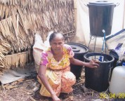 """One of our water kits set up in this ladies home. Note, that her home has a dirt floor and one wall of plastic."""